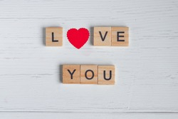 Top view of the word love you laid out from square wooden tiles and smal red hearts on old white wooden background. Concept of valentine day.