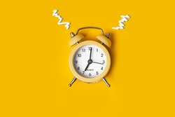 Top view of the yellow alarm clock on the yellow background with a free space for text. Getting up early in the morning. Wake up with a great mood