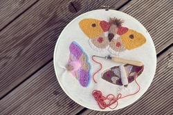 Top view of three embroidered multicolored butterflies on two-thread cloth in a hoop with punch needle and brick-red thread inside of it. Punch needle embroidery project on wooden panels.