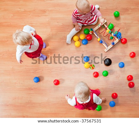 Top view of three little girls playing on the floor