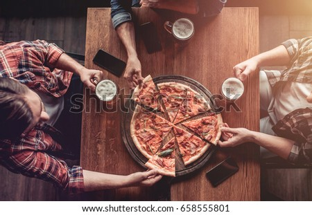 Top view of three male friends in bar drinking beer and eating pizza. stock photo