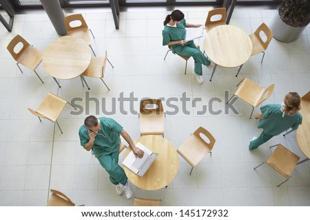 Top view of three physicians during work break in the cafeteria