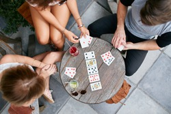Top view of three young people playing cards at sidewalk cafe. Young people sitting around a coffee table and playing card game.