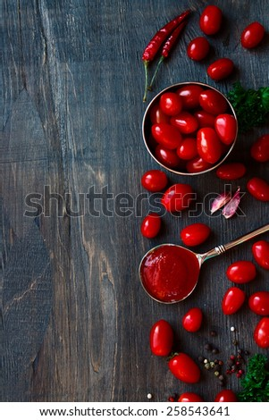 Top view of tomato sauce, tomatoes and spices on wood background with copyspace.