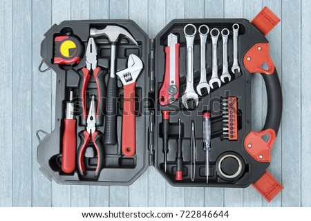 Top view of toolbox with tools on the wooden table