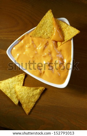 Top view of tortilla corn chips and cheese dip.