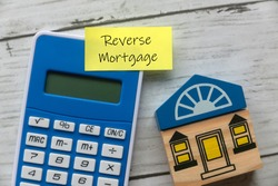 Top view of toy wooden house, calculator and sticky note written with Reverse Mortgage on white wooden background.
