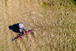 Top view of tractor with tedders, drying mowed hay