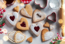 Top view of traditional Linzer cookies with raspberry jam heart on table. Christmas or Valentines day traditional homemade heart shaped cookies, tasty snack.