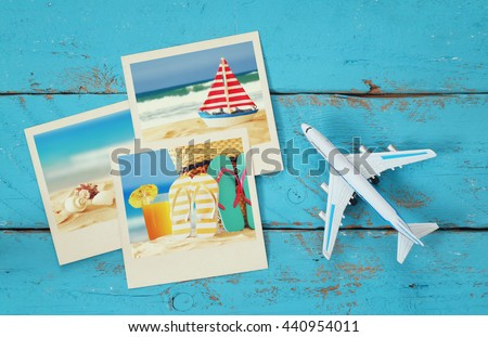 Top view of travel instant photographs next to airplane over wooden table. traveling concept