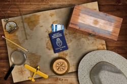 Top view of traveling gadgets, vintage map, magnify glass, hat and airplane model on the wood table background. On center, official passport of Argentina and your flag.