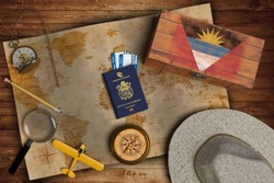 Top view of traveling gadgets, vintage map, magnify glass, hat and airplane model on the wood table background. On center, official passport of Antigua and Barbuda and your flag.