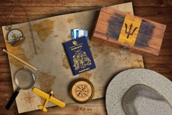 Top view of traveling gadgets, vintage map, magnify glass, hat and airplane model on the wood table background. On center, official passport of Barbados and your flag.