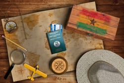 Top view of traveling gadgets, vintage map, magnify glass, hat and airplane model on the wood table background. On center, official passport of Ghana and your flag.