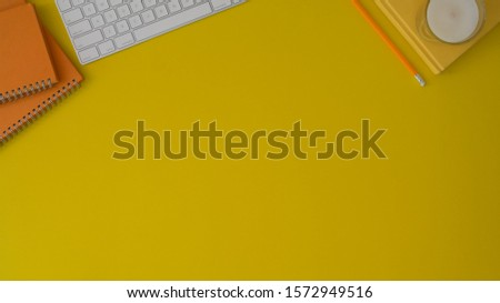 Top view of trendy workplace with copy space and copy space on yellow desk background