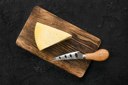 Top view of triangular piece of hard cheese on wooden cutting board