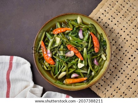 Top view of tumis genjer or tumis kelayan or tumis enceng or stir fry isolated on brown background. Foto stock ©