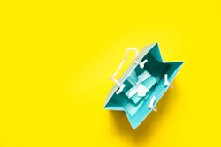 Top view of turquoise gift box with white ribbon and shopping bag on bright yellow background