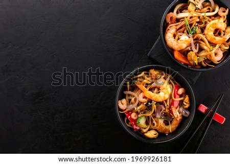 Top view of two black bowls with wok noodles with shrimps and vegetables on a slate black background, copy space. Traditional Asian food set. Zdjęcia stock ©