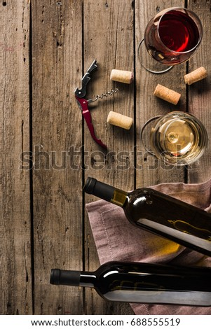 top view of two bottles of wine, corkscrew and wineglasses on wooden tabletop with copy space  #688555519