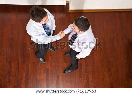 Top view of two business men giving hand shake and congratulate each other
