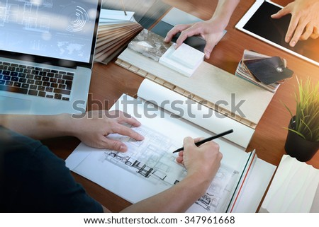 top view of two colleagues interior designers discussing data with blank screen new modern computer laptop and pro digital tablet with sample material on wooden desk as concept