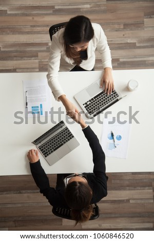 Top view of two female associates or CEOs handshaking greeting each other or making agreement and starting successful cooperation together. Concept of partnership, closing deal, women in business #1060846520