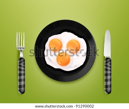 top view of two fried eggs on black Plate between silver knife and fork on gray background.