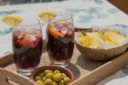 Top view of two glasses filled with red wine and soda with ice cubes and slices of lemon typical spanish on a wooden tray with a plate of olives and a bowl of potato chips on a white and green