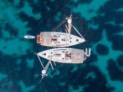 top view of two sailboats anchored at sea