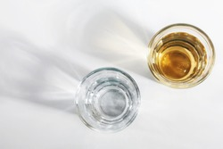 Top view of two shot glasses of Brazilian gold cachaca isolated on white background