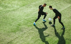 Top view of two teenagers playing football during team practice in field. Young soccer players playing on the sports grass field.