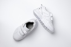 top view of two white children sneakers with velcro fasteners for easy footwear isolated on a white background.