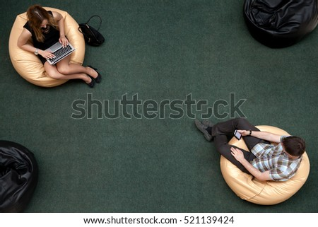 Top view of two young people, man and woman, sitting on bean bags, using electronic devices in public wifi area, working on laptop, typing, using smartphone, texting message, top view