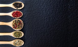 Top view of 5 types of peppercorn in a wooden spoon on a black background Healthy food concept