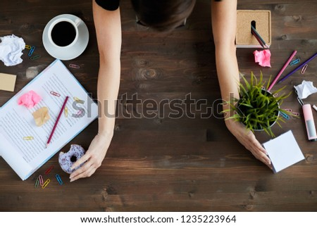 Top view of unrecognizable woman clearing up space on wooden desk, putting away stationery, papers, plant, food and other stuff