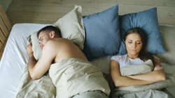 Top view of upset lying sleepless couple in bed offended because of quarrel