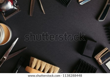 top view of various professional barber tools on black background