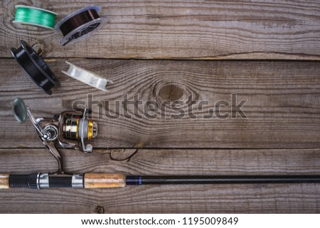 top view of various reels and fishing rod on wooden planks  #1195009849