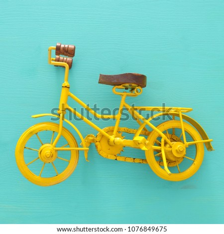 top view of vintage metal yellow bicycle toy over wooden background