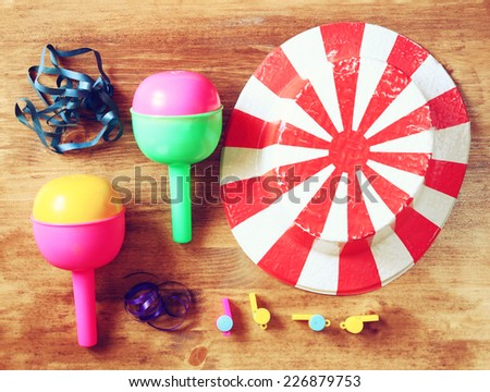 top view of vintage party  accessories - party hat maracas whistles and confetti over wooden board.