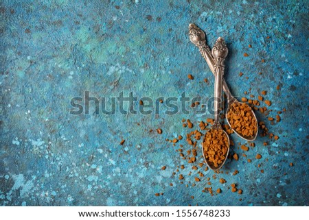 Top view of vintage silver teaspoons with granulated instant coffee on blue concrete background with copy space