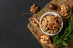 Top view of Walnut in white cup on black background. healthy nuts concept. Walnuts are an excellent source of antioxidants and including LDL cholesterol, which promotes atherosclerosis.