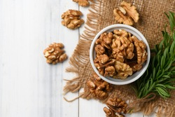 Top view of Walnut in white cup on wood background. healthy nuts concept. Walnuts are an excellent source of antioxidants and including LDL cholesterol, which promotes atherosclerosis.