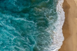 Top view of waves breaking into the sand at the beach, aerial photography, photo taking from helicopter looking down