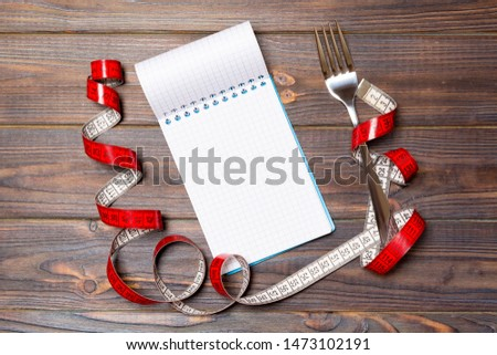 Top view of weight loss concept on dark wooden background. Mix of red centimeter tape, note pad and fork with space for your design.