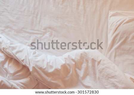 Top view of white bedding sheets and pillow at morning time (soft warm tone)