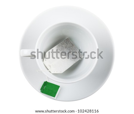 Top view of white cup with teabag over white background