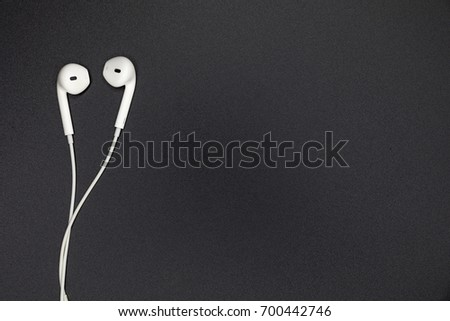 Top view of White Earphones on Black background. Copy space. Music is my life concept
