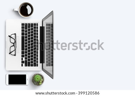 Top view of white office desk with laptop, smartphone, cup of coffee and supplies. Top view with copy space.